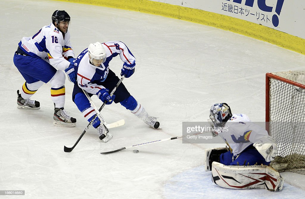 Park Woosang #26 of South Korea skates against Csaba Nagy #10 and Adrian Catrinoi #1 of Romania during the Ice Hockey Sochi Olympic Pre-Qualification Group J match between South Korea and Romania at Nikko Kirifuri Ice Arena on November 11, 2012 in Nikko, Tochigi, Japan. South Korea won 2-0.