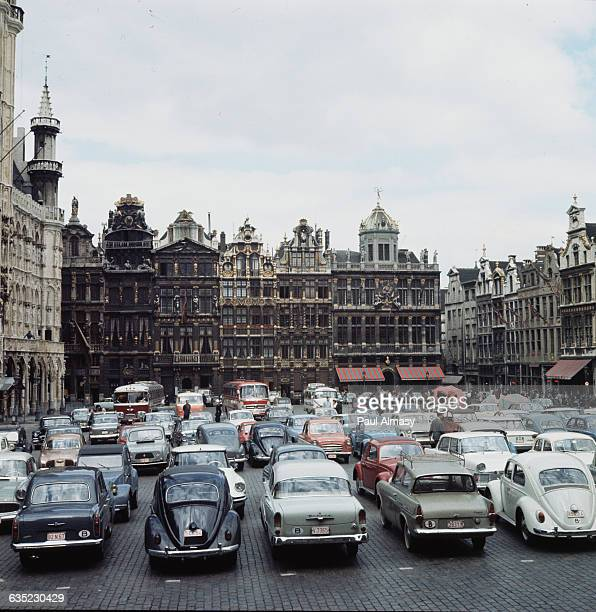 Parked cars fill a cobblestone lot near goldtrimmed buildings that surround the GrandPlace a public square in Brussels Belgium The site of many...
