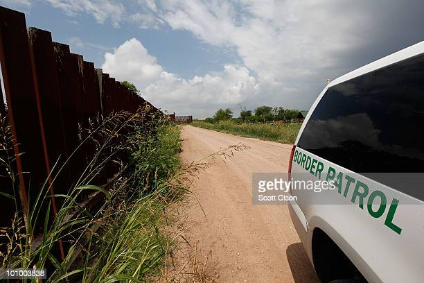 Parked next to a section of the border fence a Border Patrol agent watches an area of the USMexico border along the Rio Grande River May 26 2010 near...