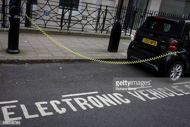 A parked Smart car recharges electric power at an EDF charging point in central London Its yellow coiled cable stretching from charging point to car...