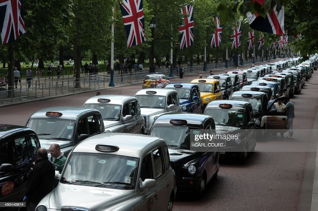 Parked taxis block the Mall leading to Buchingham Palace during a protest by London black cab drivers against a new private taxi service 'Uber', a mobile phone app, in central London on June 11, 2014. Taxi drivers brought parts of London, Paris and other European cities to a standstill on June 11 as they protested against new private cab apps such as Uber which have shaken up the industry. Thousands of London's iconic black cabs, many of them beeping their horns, filled the roads around Buckingham Palace, Trafalgar Square and the Houses of Parliament to the exclusion of any other vehicles. AFP PHOTO / CARL COURT