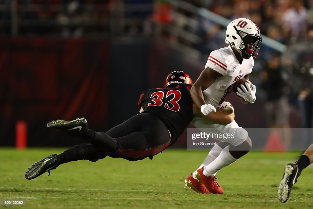 Parker Baldwin #33 of the San Diego State Aztecs tackles D.J. Brown #10 of the Northern Illinois Huskies in the third quarter during the Northern Illinois v San Diego State game at Qualcomm Stadium on September 30, 2017 in San Diego, California.