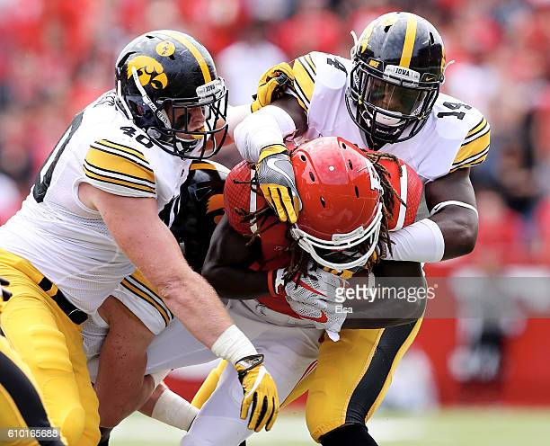 Parker Hesse and Desmond King of the Iowa Hawkeyes tackle Janarion Grant of the Rutgers Scarlet Knights in the first half at High Point Solutions...
