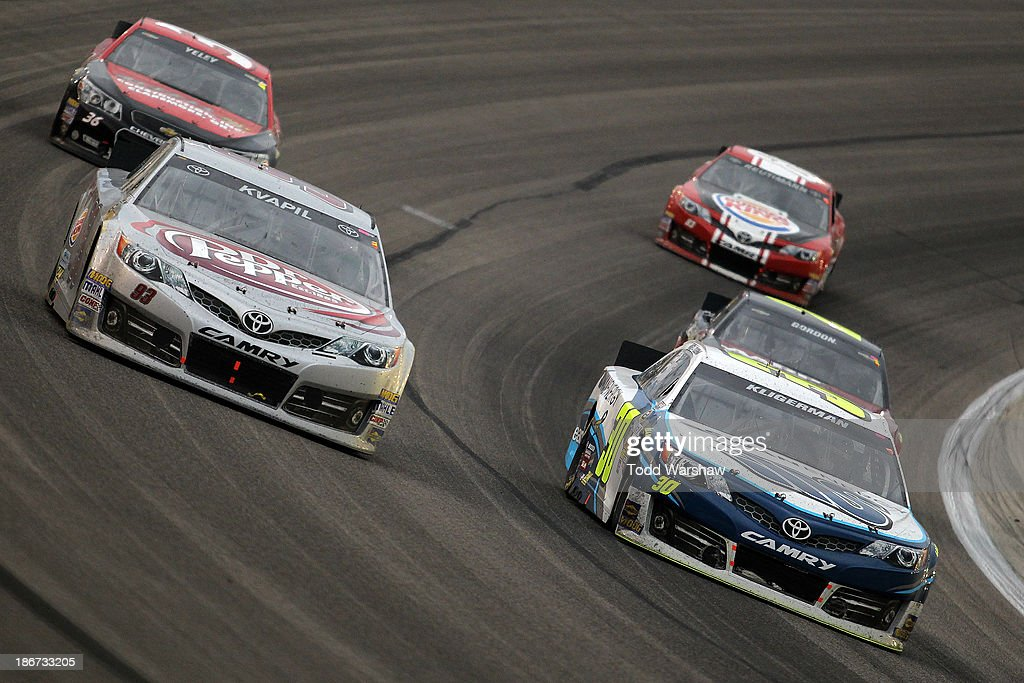 Parker Kligerman, driver of the #30 Swan Energy / Lean1 Toyota, races with Travis Kvapil, driver of the #93 Dr. Pepper / Burger King Toyota, during the NASCAR Sprint Cup Series AAA Texas 500 at Texas Motor Speedway on November 3, 2013 in Fort Worth, Texas.