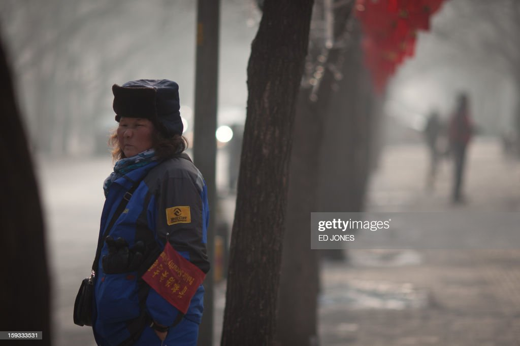 A parking attendant stands on a roadside during severe pollution in Beijing on January 12, 2013. Air quality data released via the US embassy twitter feed recorded air quality index levels so hazardous that they were classed as 'Beyond Index'. Just after midday the particle matter (PM) 2.5 figure was 519 on a scale that stops at 500, and advises against all outdoor activity. AFP PHOTO / Ed Jones