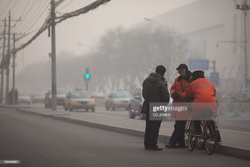 Parking attendants stand on a roadside during severe pollution in Beijing on January 12, 2013. Air quality data released via the US embassy twitter feed recorded air quality index levels so hazardous that they were classed as 'Beyond Index'. By 4pm the particle matter (PM) 2.5 figure was 728 on a scale that stops at 500 at which point the US embassy website advises against all outdoor activity. AFP PHOTO / Ed Jones