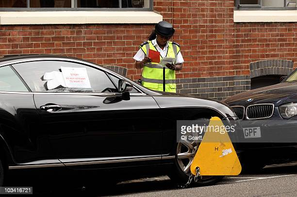 A parking enforcement officer posts notices on the car after a wheel clamp has been attached to a car in Kensington on August 17 2010 in London...