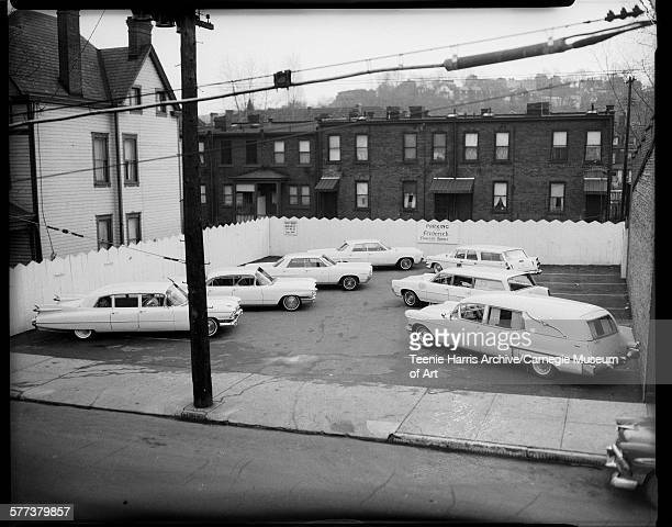 Parking lot of Frederick Funeral Home on Brushton Avenue with seven automobiles including hearses and telephone pole in left foreground Homewood...