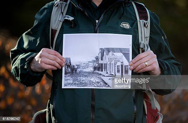 A Parks Canada government employee holds a photograph taken in 1899 of the street where 2016 Republican Presidential Nominee Donald Trump's...
