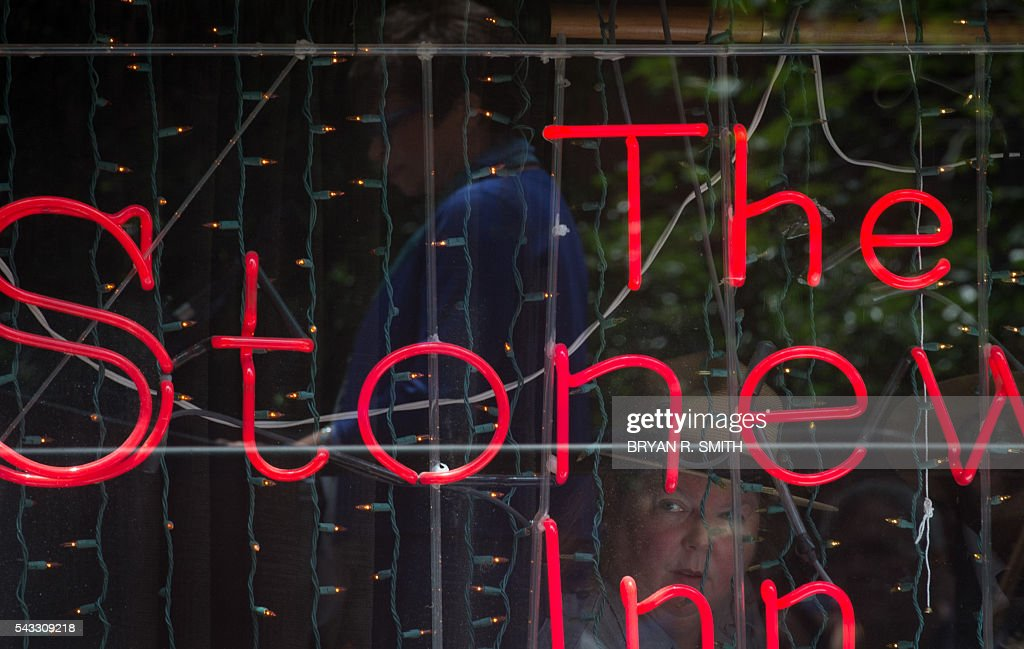 US Parks Department member Suzanne McCarthy looks out the window of the Stonewall Inn as Mayor Bill de Blasio joins elected officials, advocates and New Yorkers in designating Stonewall Inn a National Monument on June 27, 2016 in New York. / AFP / Bryan R. Smith