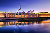 Australian national parliament house in Canberra. Facade of the buidling brightly illuminated and reflecting in blurred water of fountain pond under waving national flag on flagpole at sunset.