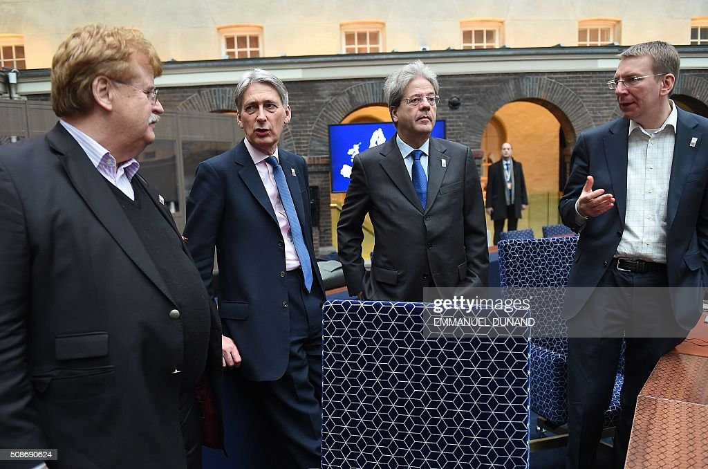 EU Parliament member Elmar Brok, British Foreign Minister Philip Hammond, Italy's Foreign Minister Paolo Gentiloni and Latvia's Foreign Minister Edgars Rinkevics speak together ahead of a EU foreign ministers meeting in Amsterdam, on February 6, 2016. The European Union on Wednesday finally reached agreement on how to finance a three-billion-euro ($3.3-billion) deal to aid Syrian refugees in Turkey, in exchange for Ankara's help in stemming the flow of migrants. / AFP / EMMANUEL DUNAND