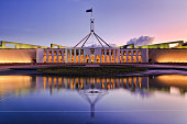 colourful reflection of Canberra's new parliament building in a fontain pond at sunset.