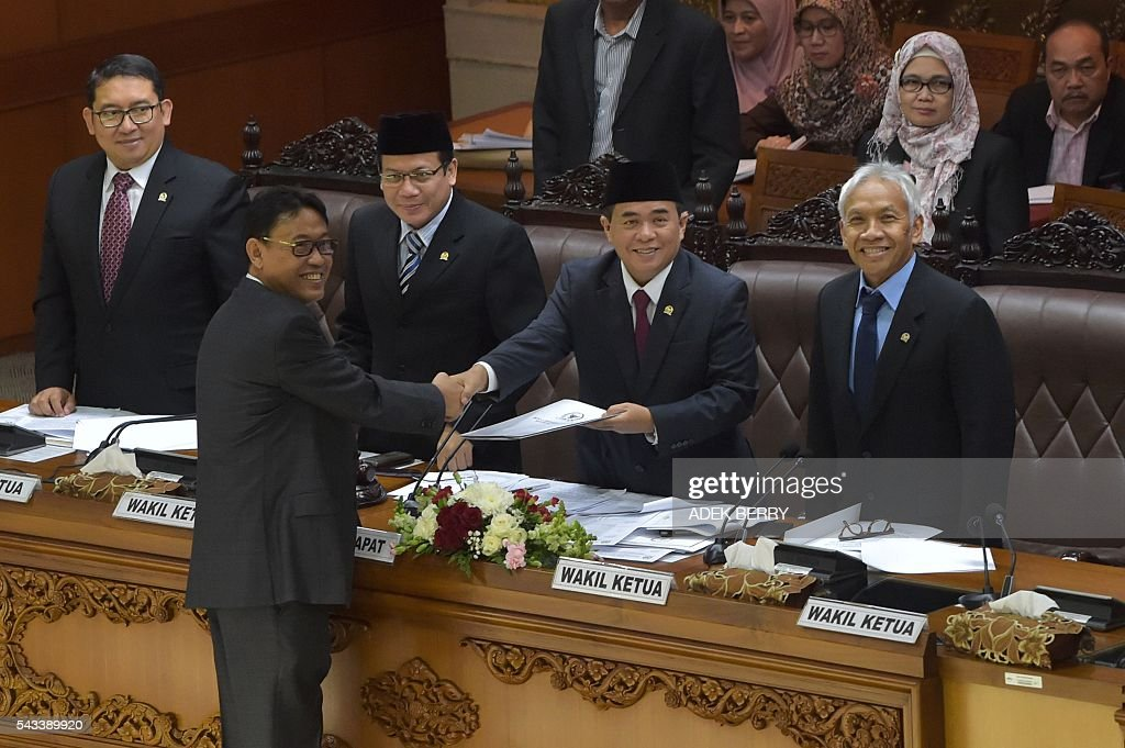 Parliament speaker Ade Komarudin (2nd R) receives a draft tax amnesty bill as lawmakers hold a plenary session at the parliament in Jakarta on June 28, 2016. Indonesia's parliament on June 28 passed a tax amnesty bill in a bid to give Southeast Asia's top economy a multi-billion-dollar boost, defying criticism the move will let evaders off the hook. BERRY