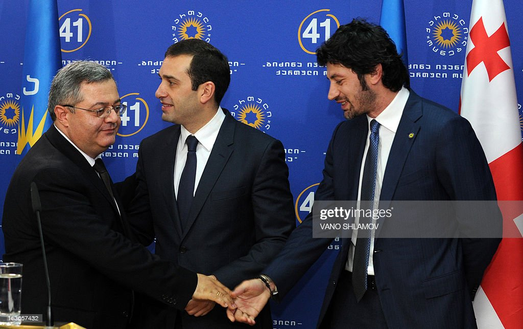 Parliament Speaker David Usupashvili (L) shakes hands with new Infrastructure and Regional Development Minister Kakha Kaladze (R), former AC Milan football star, on October 8, 2012 as new Defense Minister Irakli Alasania (C) walks past them during a presentation ceremony of new members of the government in Tbilisi. Kaladze has enjoyed the peak of football success but his latest triumph in the October 1 elections may see him making his debut on unfamiliar ground as the country's deputy prime minister. Twice winner of the Champions League with Italy's AC Milan, Kaladze has been nominated as vice-premier and minister of regional development and infrastructure in the next government after the Georgian Dream coalition's shock victory in last week's parliamentary polls. Man at left is unidentified. AFP PHOTO/VANO SHLAMOV
