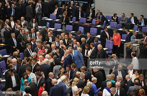 Parliamentarians including German Chancellor Angela Merkel cast their ballots during votes over the third EU financial aid package to Greece at an...