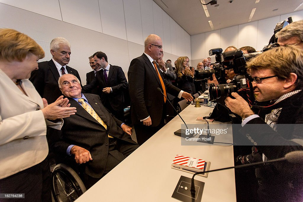 Parliamentarians of the German Christian Democrats and German Chancellor Angela Merkel welcome former German Chancellor Helmut Kohl at the Bundestag...