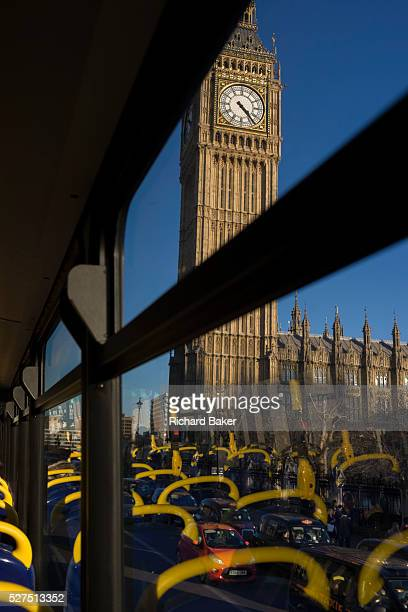 Parliament's Big Ben is seen through the top deck window of a London doubledecker bus Its yellow seating handles are seen as reflections as traffic...