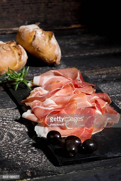 Parma ham and black olives on chopping board, dark wood
