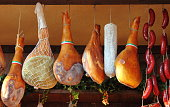 Parma Ham hanging in a delicatessen shop in Italy