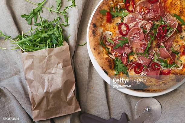 Parma ham pizza with rocket and paper bag with rocket