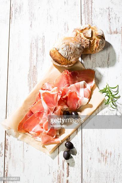 Parma ham, rolls and black olives, greaseproof paper on bright wood