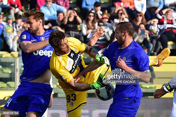 Parma's goalkeeper Antonio Mirante grabs the ball next to Juventus' defender Giorgio Chiellini and Juventus' forward from Spain Fernando Llorente...