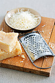 Parmesan cheese and grater on cutting board at table