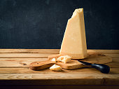 Parmesan cheese on wooden table over black stone background