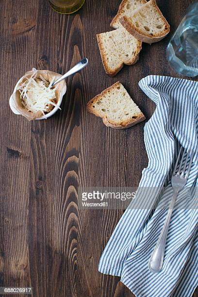 Parmesan, slices of white bread, cloth and fork on dark wood