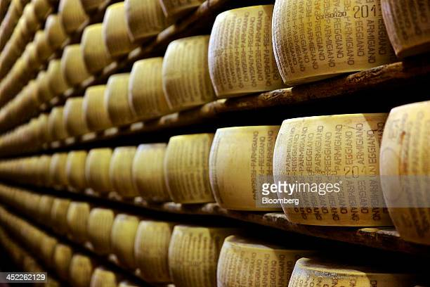 Parmigiano Reggiano cheeses sit on storage racks during the aging process at Il Trionfo cheese makers in San Secondo Parmense Italy on Tuesday Nov 26...