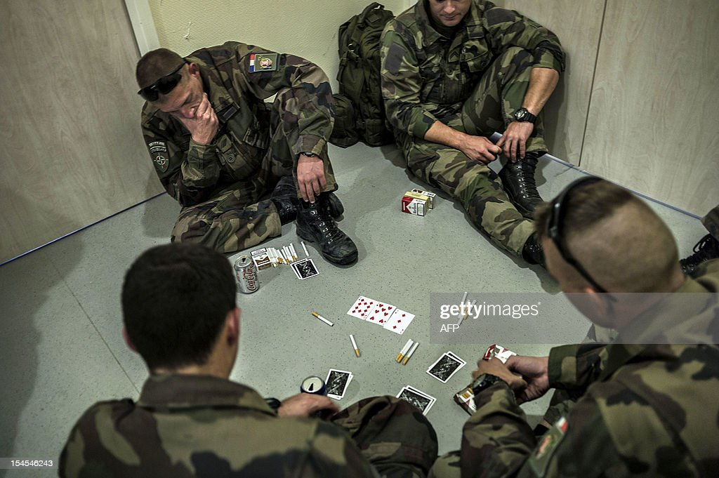 Part 16th BC French unit soldiers play poker as they wait for their plane to France on September 29, 2012 at KAIA airport in Kabul. The withdrawal of French combat troops from Afghanistan will happen 'a bit more quickly than anticipated' and could be completed before the end of December, France's Foreign Minister Laurent Fabius said on October 20, 2012.