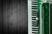 Part green accordion on wooden grey background. Write text.