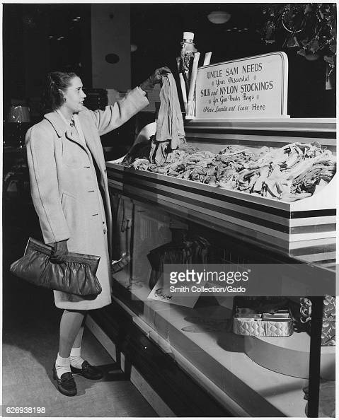 Part of a campaign to collect used nylon stockings for American efforts during World War II a young woman holds up a pair of disbanded stockings that...