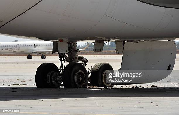 Part of a damaged aircraft at Tripoli International Airport is seen in Tripoli Libya on September 11 2014 A great number of aircrafts and service...