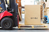 a large photograph of the part of the forklift in the form of a wheel and forks on which you lay a pallet with a large cortone box.