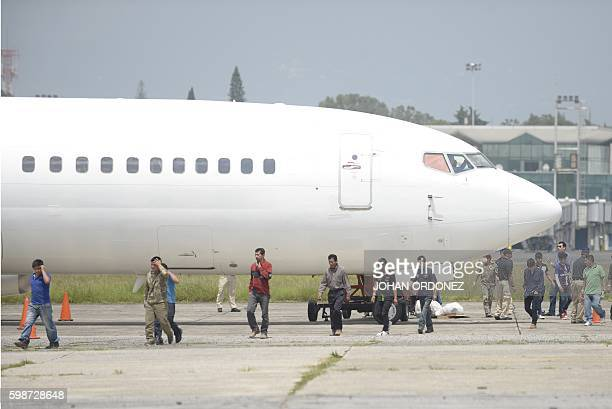 Part of a group of 98 deported Guatemalans walk across the apron upon arriving at the Air Force base in Guatemala City outbound from Arizona on...