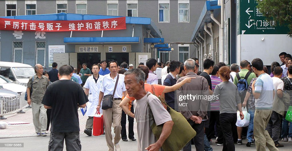Part of a line of people wait to buy tickets for appointments at the east campus of the Peking Union Medical College Hospital. A crowd began to gather around the line as a fight broke out on September 8, 2010. The red sign to the left forbids the reselling of tickets and exhorts people to 'keep harmonious order.'