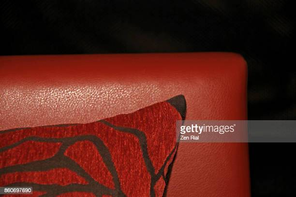 Part of a throw pillow on leather chair against black background