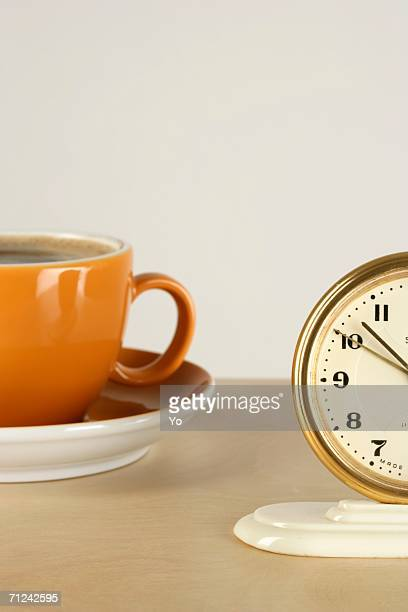 Part of an alarm clock and a cup of coffee