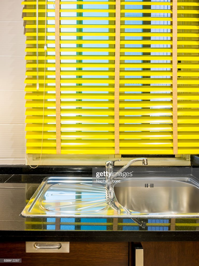 Part of colorful slim-line blind over sink in modern kitchen : Stock Photo