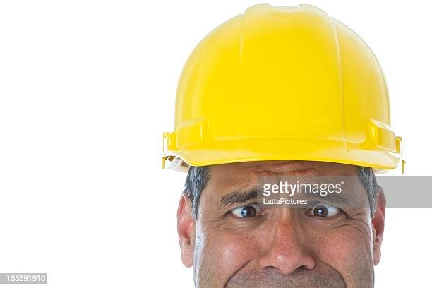Part of Hispanic male wearing hard hat making a face
