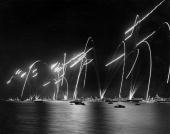 Part of the Coronation Naval Review with the fleet lit up and flares set off overhead to celebrate Elizabeth II's coming to the British throne
