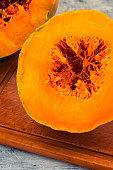 Part of the cut ripe pumpkin, orange pulp and fiber in the core.