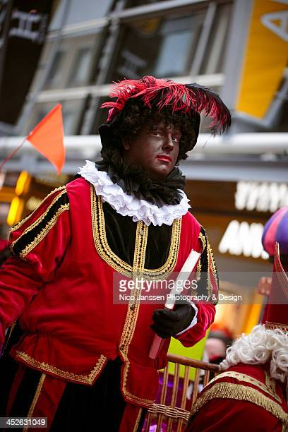 CONTENT] Part of the Dutch Saint Nicholas celebration a serious Black Pete marches in the parade through Almere carrying the Sint's book of names Een...