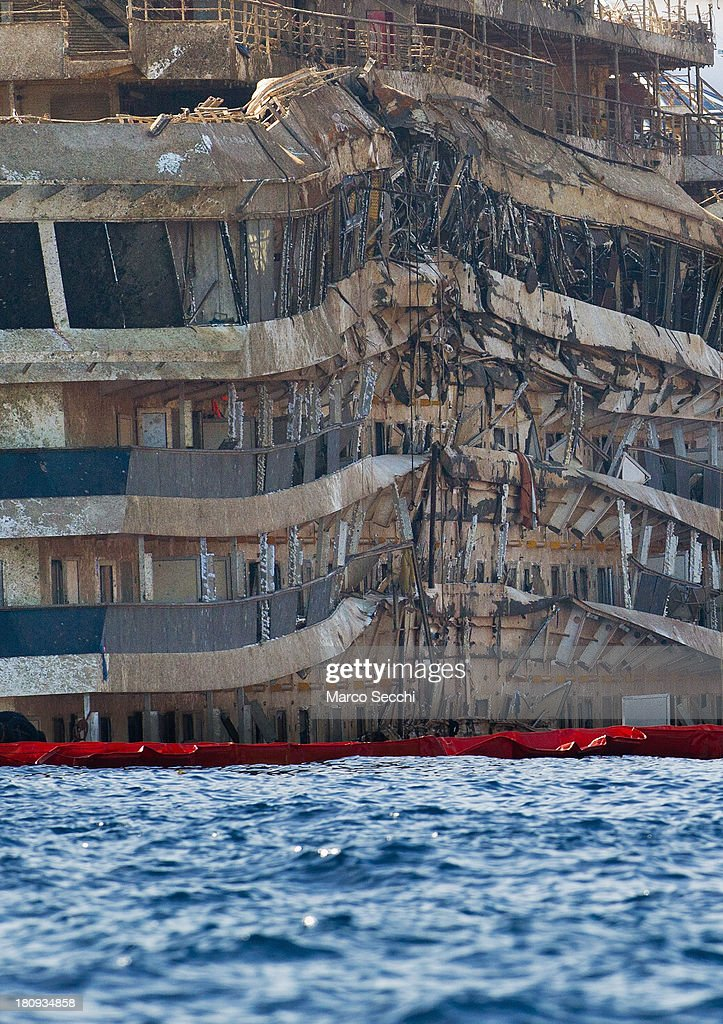 Part of the previously submerged, severely damaged right side of the Costa Concordia cruise ship is seen in upright position on September 18, 2013 in Isola del Giglio, Italy. The vessel, which sank on January 12, 2012, was successfully righted during a painstaking operation yesterday morning. The ship will eventually be towed away and scrapped. It was the first time the procedure, known as parbuckling, had been carried out on a vessel as large as Costa Concordia.