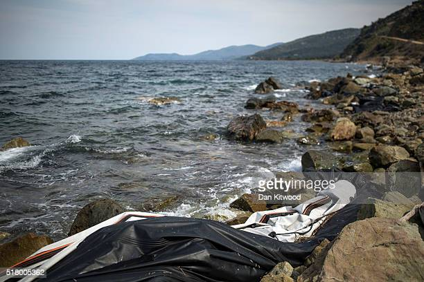 A part of the shoreline is littered with rubber boats under a cliff face on March 29 2016 in Skala Sikamineas Greece Most of the discarded boats and...