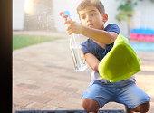 Shot of a little boy washing a glass door at home