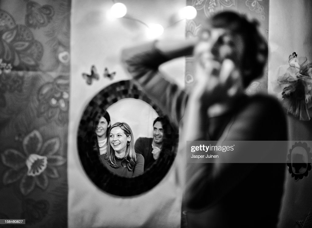 A part of the tiny public is reflected in a mirror on the wall as actress Aixa Villagran performs during her 'Manual de orgasmos fingidos' micro theater show at the 'Micro Teatro por Dinero' on December 15, 2012 in Madrid, Spain. In November 2009, fifty artists presented a theatre project in the thirteen rooms of a former brothel, two weeks before its demolition, with each function lasting less than 10 minutes. The initiative was a huge success, with more people queueing up outside than could enter. Today's 'Micro Theatre For Money' is named after the former brothel on Ballesta Street, and offers a cheap and original way for going out at night, especially in times of financial hardship. With each show priced at 4 Euros, over 150,000 spectators have already attended performances at the tiny theatre in the Malasana area. Anyone can submit a project to be chosen to perform for a month in one of the five tiny rooms in the basement of the theatre, making it an ideal platform for young Spanish authors and actors, often unemployed, to perform.