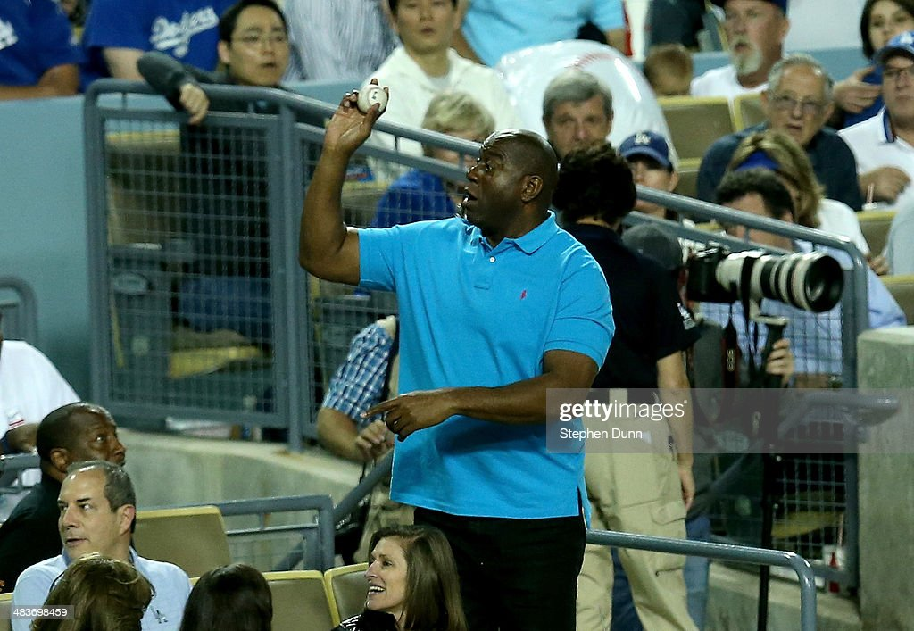 Part owner <a gi-track='captionPersonalityLinkClicked' href=/galleries/search?phrase=Magic+Johnson&family=editorial&specificpeople=157511 ng-click='$event.stopPropagation()'>Magic Johnson</a> of the Los Angeles Dodgers throws a ball that was fouled into his box to fans during the game the Detroit Tigers at Dodger Stadium on April 9, 2014 in Los Angeles, California.